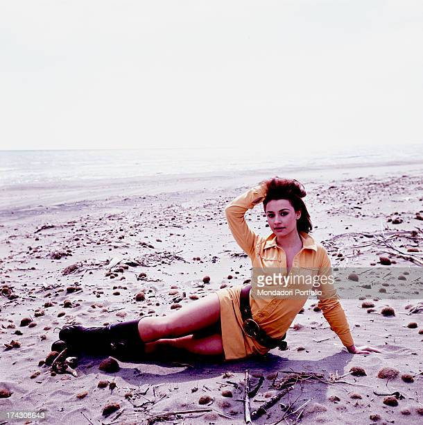 The Italian showgirl Raffaella Carrà is lying on the beach She is wearing a yellow minidress a belt and a pair of boots Italy the '70s