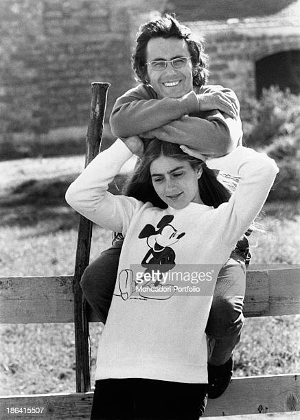 The Italian singer Al Bano born Albano Carrisi and the American actress Romina Power photographed in a tender attitude next to a fence of their...