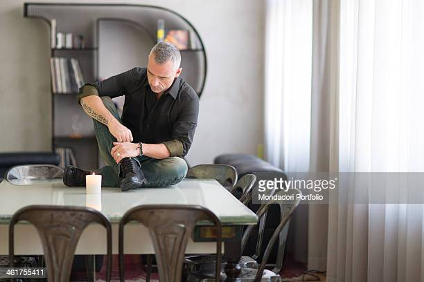 The Italian singer Eros Ramazzotti sitting on the table face down and the arm resting on the leg during a photo shoot done in his own recording...