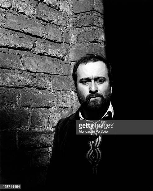 The Italian singer Lucio Dalla poses in front of the photographer with his eyeglasses' side between his lips next to the walls of the Sforzesco...