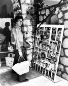 The Italian singer Peppino di Capri posing with a straw bag in his hand in front of a stand of souvenirs Capri 1970s
