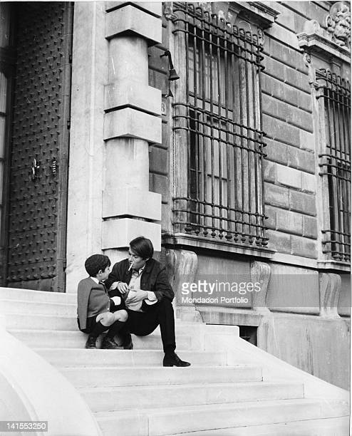 The Italian singersongwriter Fabrizio De Andre sitting on a flight of steps with the son Cristiano 1960s