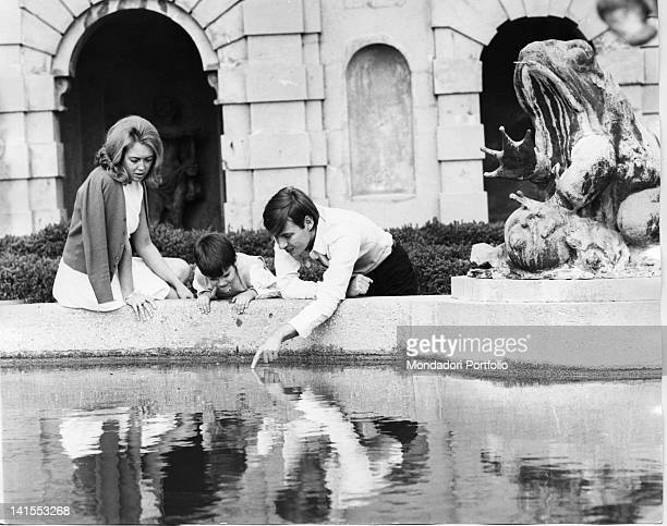 The Italian singersongwriter Fabrizio De Andre with son Cristiano and wife Puny playing on the rim of a fountain Genoa 1968