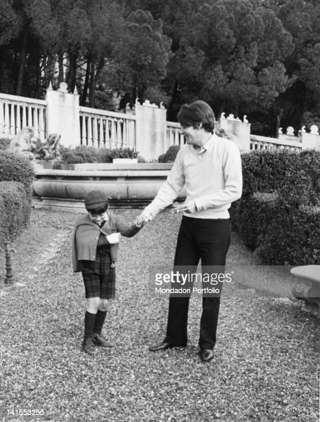 The Italian singersongwriter Fabrizio De AndrT strolling in the garden of his mansion with son Cristiano Genoa 1968