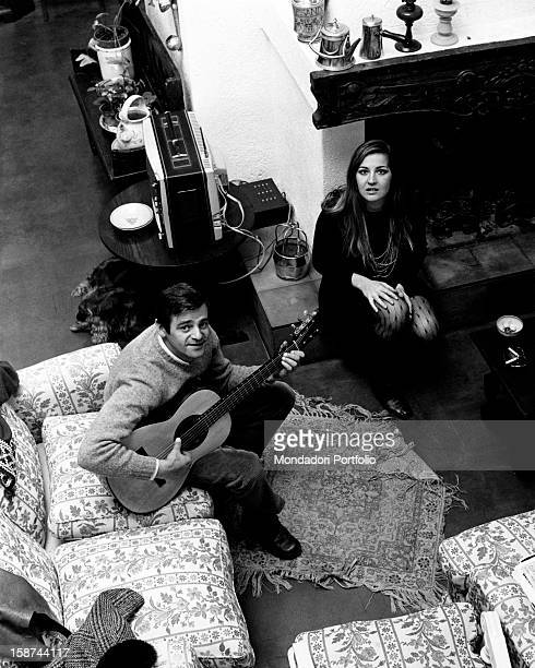 The Italian songwriter Sergio Endrigo is playing guitar next to his wife Lula in the livingroom of their house Casali di Mentana Rome Italy 1968