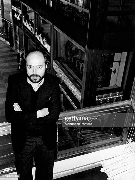 The Italian stylist Elio Fiorucci poses standing with his arms crossed and looking at the camera on the background his first boutique in Milan...