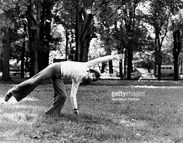 The Italian television anchor and author Paolo Limiti is doing a cartwheel in a park Milan 1973