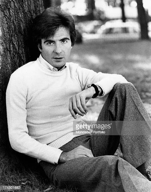 The Italian television anchor and author Paolo Limiti is sitting on the grass leaning against a tree trunk of a park tree Milan 1973
