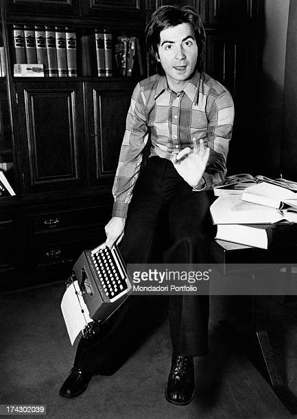 The Italian television anchor and author Paolo Limiti is talking and gesticulating leaning on his study desk with a typewriter in his hand Milan 1973