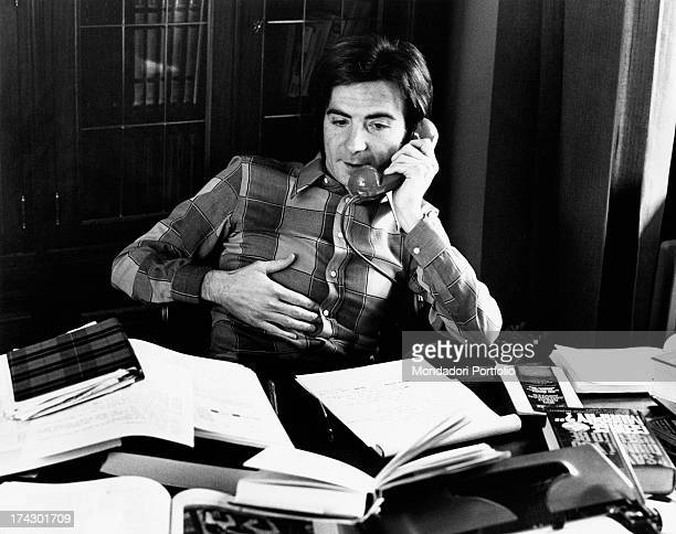 The Italian television anchor and author Paolo Limiti on the phone sitting at his desk which is cluttered with books and notes Milan 1973