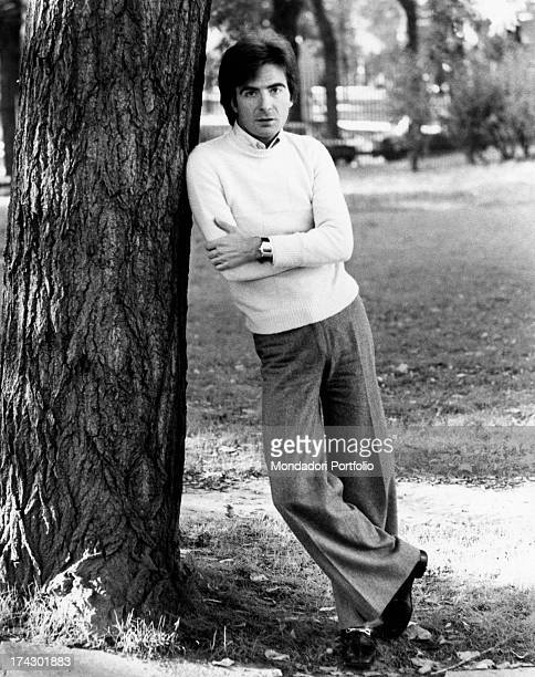 The Italian television anchor and author Paolo Limiti with his arms crossed poses leaning against a park tree trunk Milan 1973