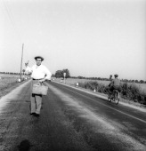 The Italian tv presenter Enzo Tortora standing on a countryside road wearing a straw hat and a holding a bag in his left hand sticks out his right...
