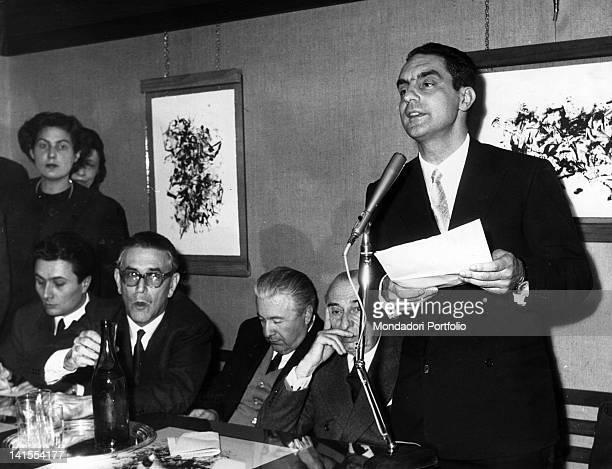 The Italian writer Italo Calvino speaking into a microphone next to the writers Alberto Arbasino Mario Soldati e Carlo Muscetta 1960s
