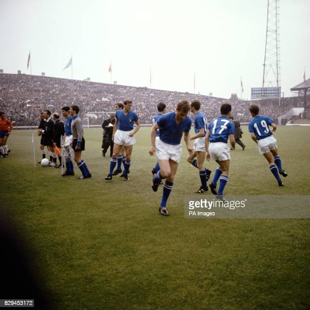 The Italy players warm up as the two teams line up before the match