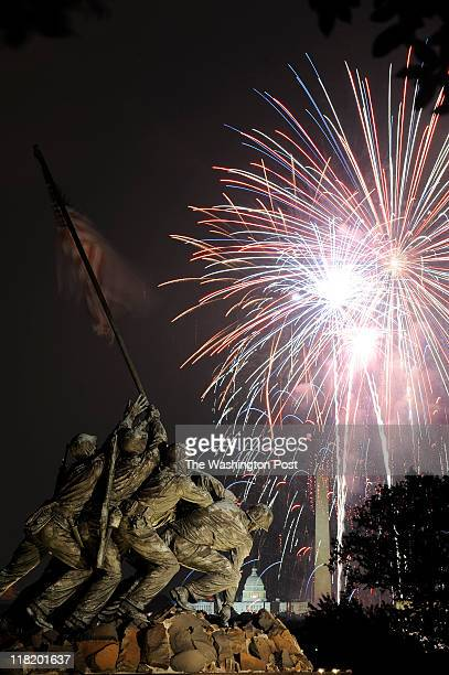 The Iwo Jima Memorial also known as the US Marine Corps War Memorial is seen along with the US Capitol and the Washington Monument as fireworks from...