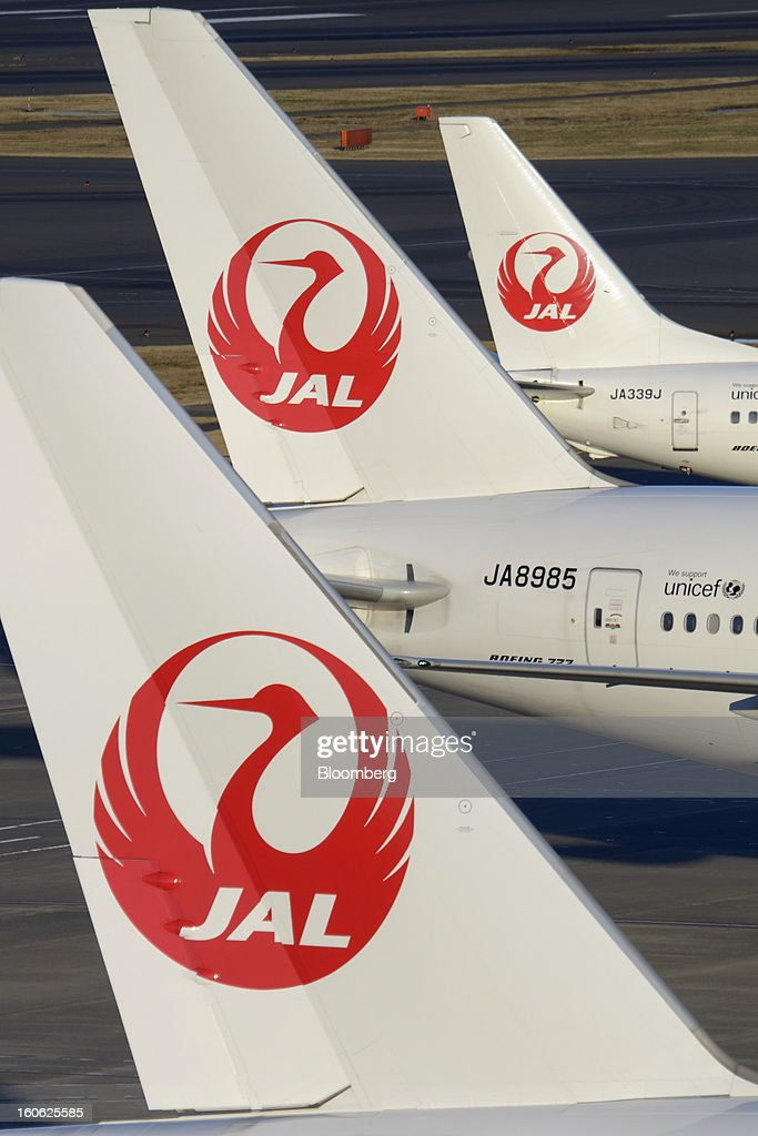 The Japan Airlines Co. (JAL) logo is displayed on the tails of aircraft parked at Haneda Airport in Tokyo, Japan, on Sunday, Feb. 3, 2013. Japan Airlines, the nation's largest carrier by market value, is scheduled to release earnings on Feb. 4. Photographer: Akio Kon/Bloomberg via Getty Images