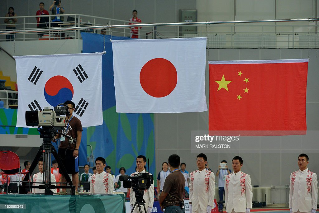 The Japanese flag is raised after Hiroto Hasegawa and Yu Okamoto won gold in the Men's Synchronized 3m Springboard Final at the East Asian Games held at the Tianjin Olympic Center Diving Hall in Tianjin on October 9, 2013. The East Asian Games which are held every four years see nine countries including China, Japan, South and North Korea participating in 262 events in 22 different sports. AFP PHOTO / Mark RALSTON