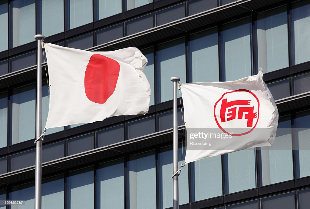 The Japanese national flag, left, and the Toyota Motor Corp. corporate flag fly outside the company's headquarters in Toyota City, Aichi Prefecture, Japan, on Friday, Jan. 18, 2013. Toyota, poised to regain its title as the world's biggest carmaker this year, said last month its vehicle sales may rise 2 percent next year to a record, led by demand from overseas markets. Photographer: Tomohiro Ohsumi/Bloomberg via Getty Images