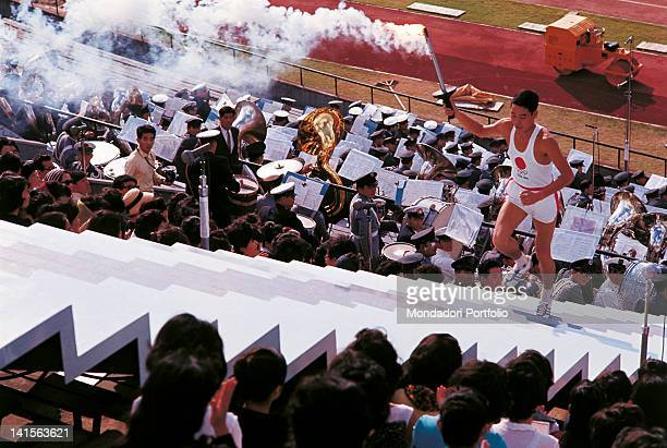 The Japanese Yoshinori Sakai the last torch bearer of the opening ceremony is climbing the stairs of the Olympic National Stadium to light the fire...