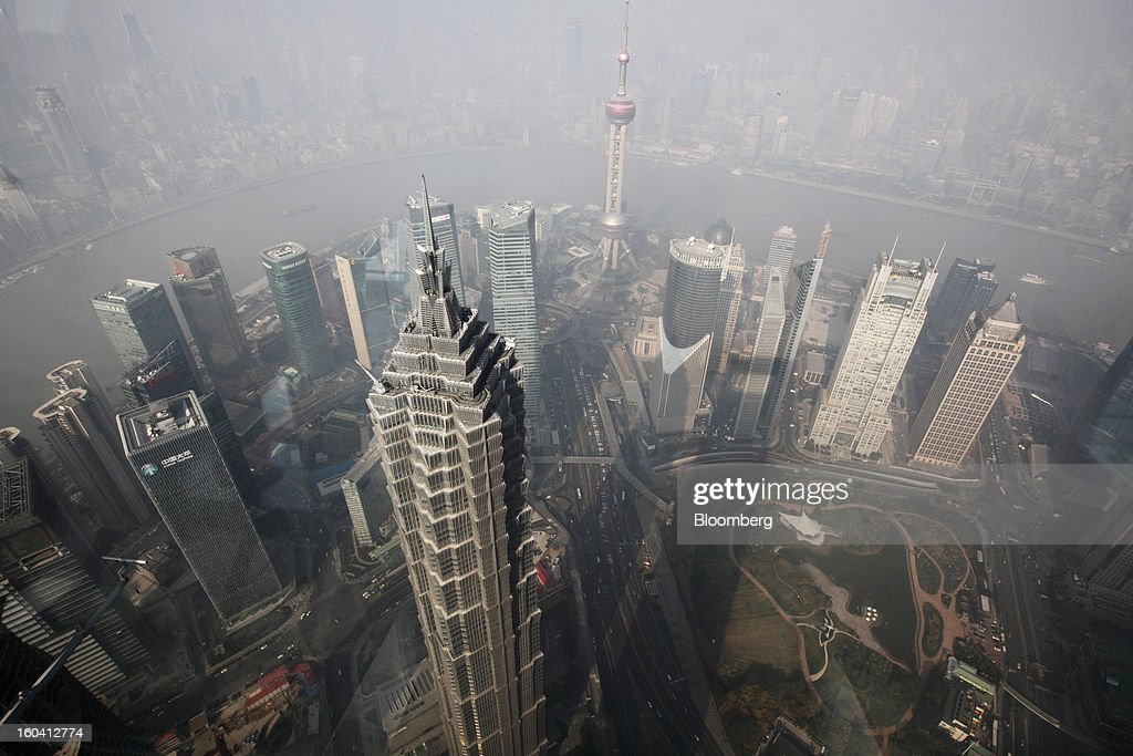 The Jin Mao Tower, center left, and the Oriental Pearl Tower, background center right, stand among other commercial buildings, seen from the Shanghai World Financial Center, in the Pudong area of Shanghai, China, on Wednesday, Jan. 30, 2013. China's economic growth accelerated for the first time in two years as government efforts to revive demand drove a rebound in industrial output, retail sales and the housing market. Photographer: Tomohiro Ohsumi/Bloomberg via Getty Images