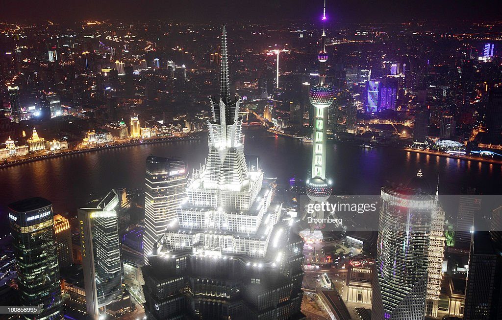 The Jin Mao Tower, center left, and the Oriental Pearl Tower, center right, stand among other commercial buildings as seen from the Shanghai World Financial Center at night in the Pudong area of Shanghai, China, on Saturday, Feb. 2, 2013. China's economic growth accelerated for the first time in two years as government efforts to revive demand drove a rebound in industrial output, retail sales and the housing market. Photographer: Tomohiro Ohsumi/Bloomberg via Getty Images