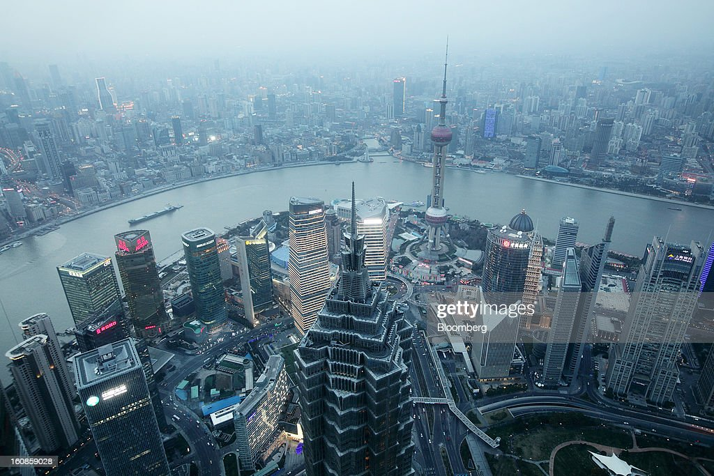 The Jin Mao Tower, center left, and the Oriental Pearl Tower, center right, stand among other commercial buildings as seen from the Shanghai World Financial Center in the Pudong area of Shanghai, China, on Saturday, Feb. 2, 2013. China's services industries grew at the fastest pace since August as gains in retailing and construction aid government efforts to drive a recovery in the world's second-biggest economy. Photographer: Tomohiro Ohsumi/Bloomberg via Getty Images