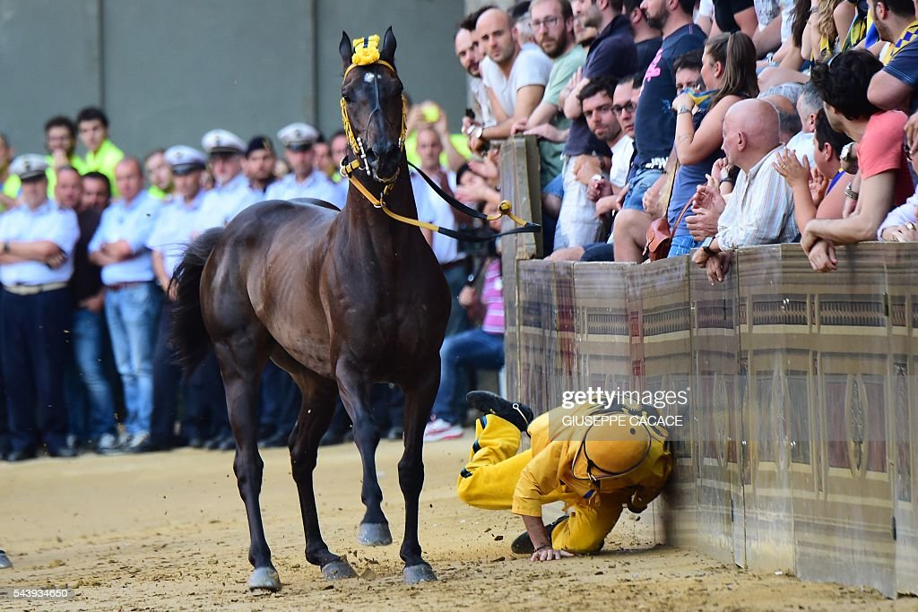 The jockey of the 'Contrada of Aquila ' falls during a proof-race of the historical Italian horse race of the Palio of Siena on June 30, 2016 in Siena. / AFP / GIUSEPPE