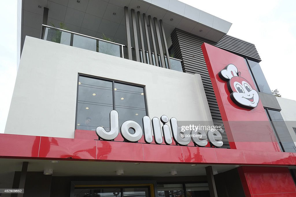 The Jollibee Foods Corp. logo is displayed outside one of the company's restaurants in Quezon City, Metro Manila, the Philippines, on Monday, July 28, 2014. Jollibee, which outsells McDonald's Corp. in the Philippines, plans to double earnings in five years as it accelerates its expansion in China and seeks an acquisition in the U.S. Photographer: Veejay Villafranca/Bloomberg via Getty Images