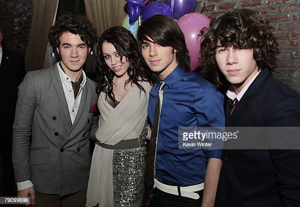 The Jonas Brothers Kevin Joe and Nick pose with actress/singer Miley Cyrus at the afterparty for the premiere of Walt Disney Pictures' 'Hannah...