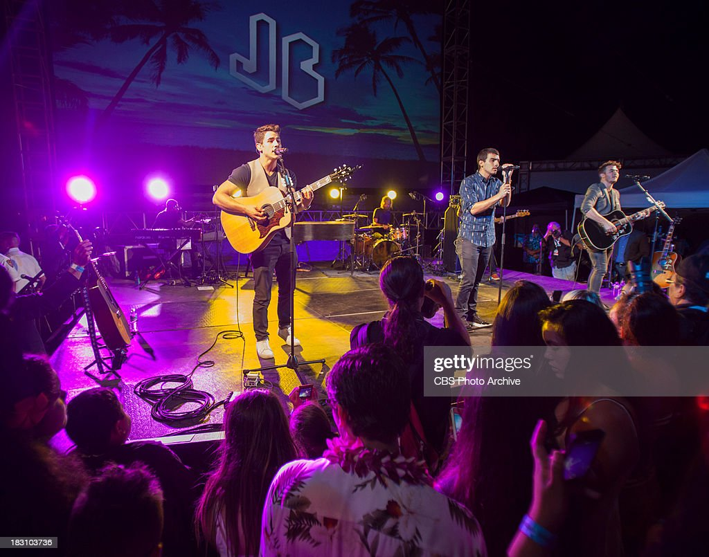 The Jonas Brothers perform at the season four premiere of Hawaii Five-0 on Queen's Beach Thursday, Sept. 26, 2013, in Waikiki, Hawaii. Thousands of Hawaii residents and visitors viewed the first episode on a big movie screen.