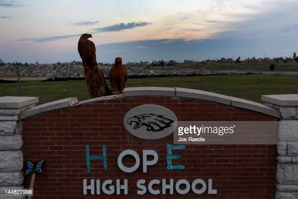 The Joplin High School sign is seen in front of the rubble of the school after the letters H and E were placed on it reading 'Hope' as the town...