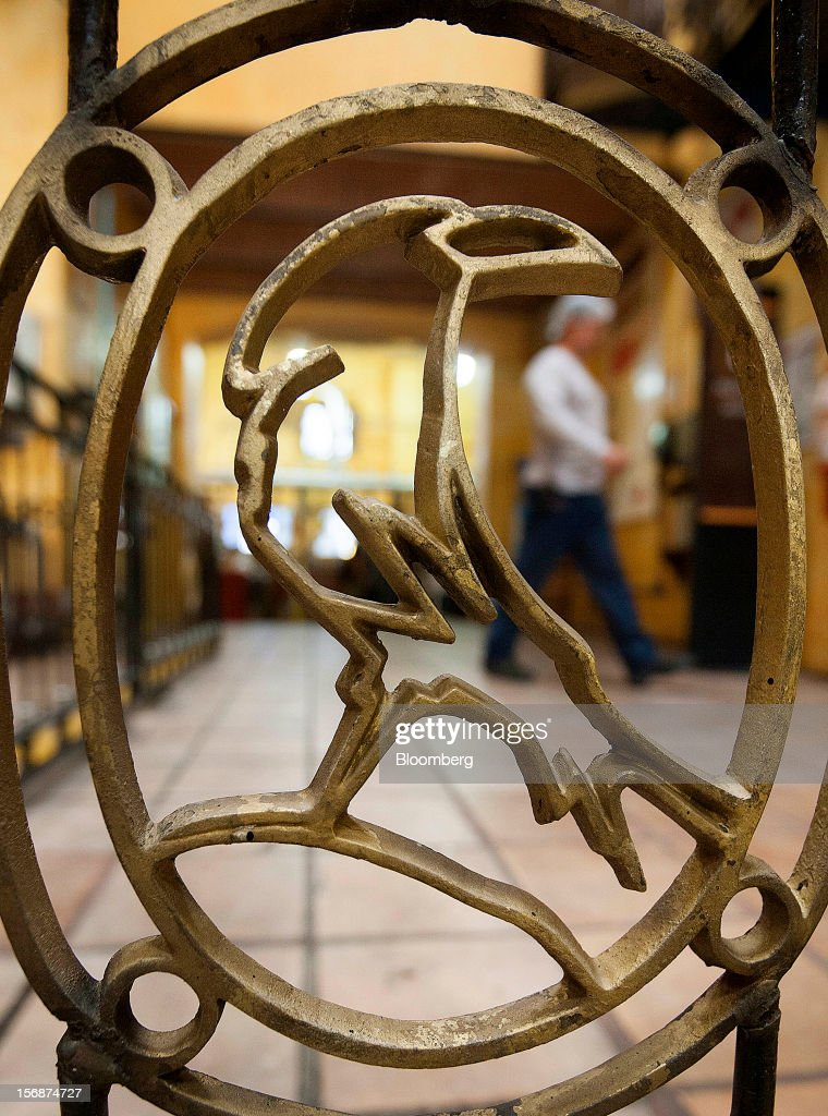 The Jose Cuervo logo is seen on a gate as a worker walks past at the Tequila Cuervo La Rojena S.A. de C.V. distillery plant in Guadalajara, Mexico, on Thursday, Nov. 22 2012. There are more than 200 types of agave in Mexico, but use of the blue agave plant was made compulsory in the last century to the issuance of the Official Mexican Standard for Tequila production. Photographer: Susana Gonzalez/Bloomberg via Getty Images