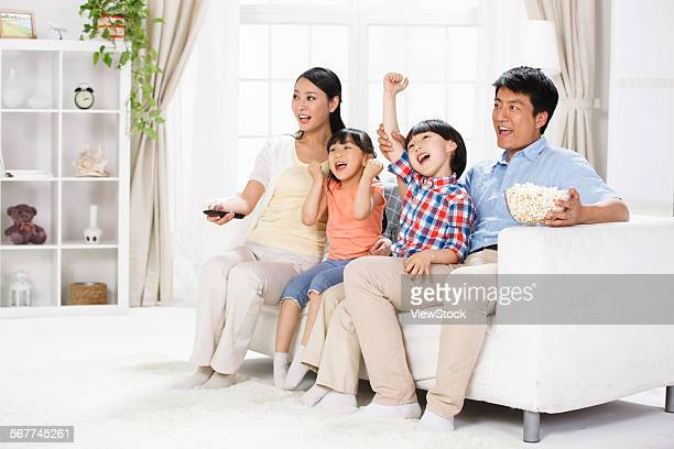 The joy of a family of four in the living room to watch TV