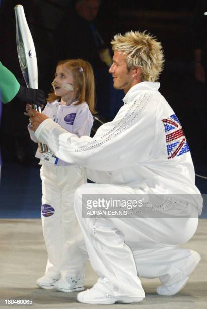 The Jubilee Baton is handed to Britain's Queen Elizabeth II by sixyear old Kirsty Howard accompanied by British soccer player David Beckham during...