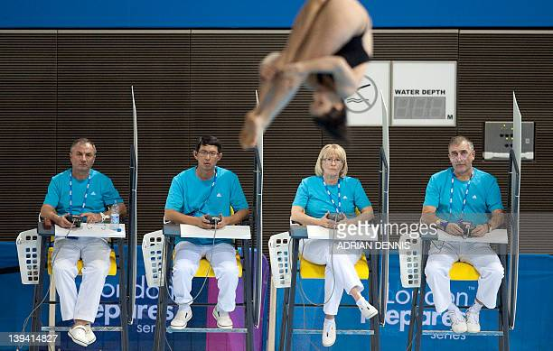 The judges look on as a diver competes during the women's 10m platform Preliminary event at the FINA Diving World Cup also doubling as a 2012...