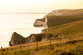 A view of the World Heritage Site, the Jurassic Coast, as seen from the hills above Durdle Door and Lulworth Cove. Shortly after sunset, the distant peninsula of Weymouth and Portland Bill are backlit