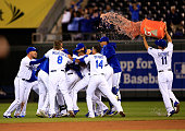 The Kansas City Royals celebrate as they swarm Lorenzo Cain who hit the gamewinning single to knock in Terrance Gore as they defeat the Chicago White...