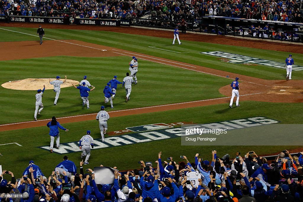 The Kansas City Royals dugout runs onto the field to celebrate with Wade Davis #17 after defeating the New York Mets in Game Five of the 2015 World Series at Citi Field on November 1, 2015 in the Flushing neighborhood of the Queens borough of New York City. The Kansas City Royals defeated the New York Mets with a score of 7 to 2.
