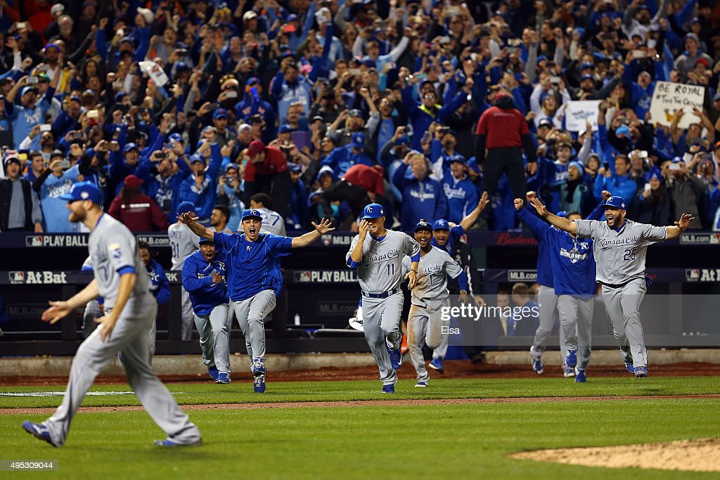 The Kansas City Royals dugout runs to the field to celebrate with Wade Davis #17 after defeating the New York Mets in Game Five of the 2015 World Series at Citi Field on November 1, 2015 in the Flushing neighborhood of the Queens borough of New York City. The Kansas City Royals defeated the New York Mets with a score of 7 to 2.