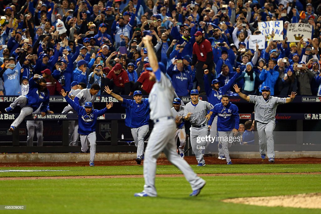 The Kansas City Royals dugout runs to the field to celebrate with Wade Davis after defeating the New York Mets in Game Five of the 2015 World Series...