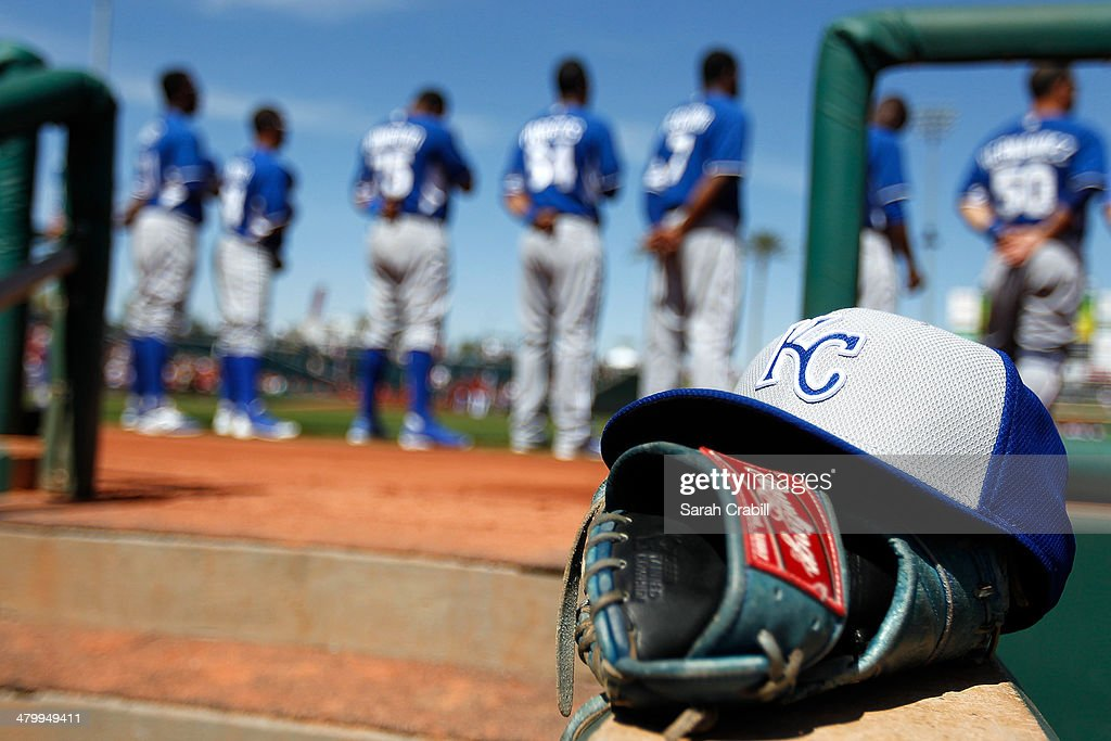 The Kansas City Royals line up during the national anthem before a game against the Cincinnati Reds at Goodyear Ballpark on March 21 2014 in Goodyear...
