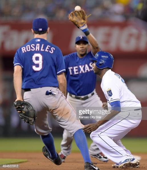 The Kansas City Royals' Lorenzo Cain right is caught in a rundown as Texas Rangers shortstop Adam Rosales tosses the ball to shortstop Elvis Andrus...