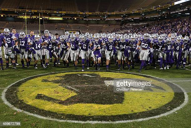 The Kansas State Wildcats run off the field arm in arm after winning the Buffalo Wild Wings Bowl against the Michigan Wolverines at Sun Devil Stadium...