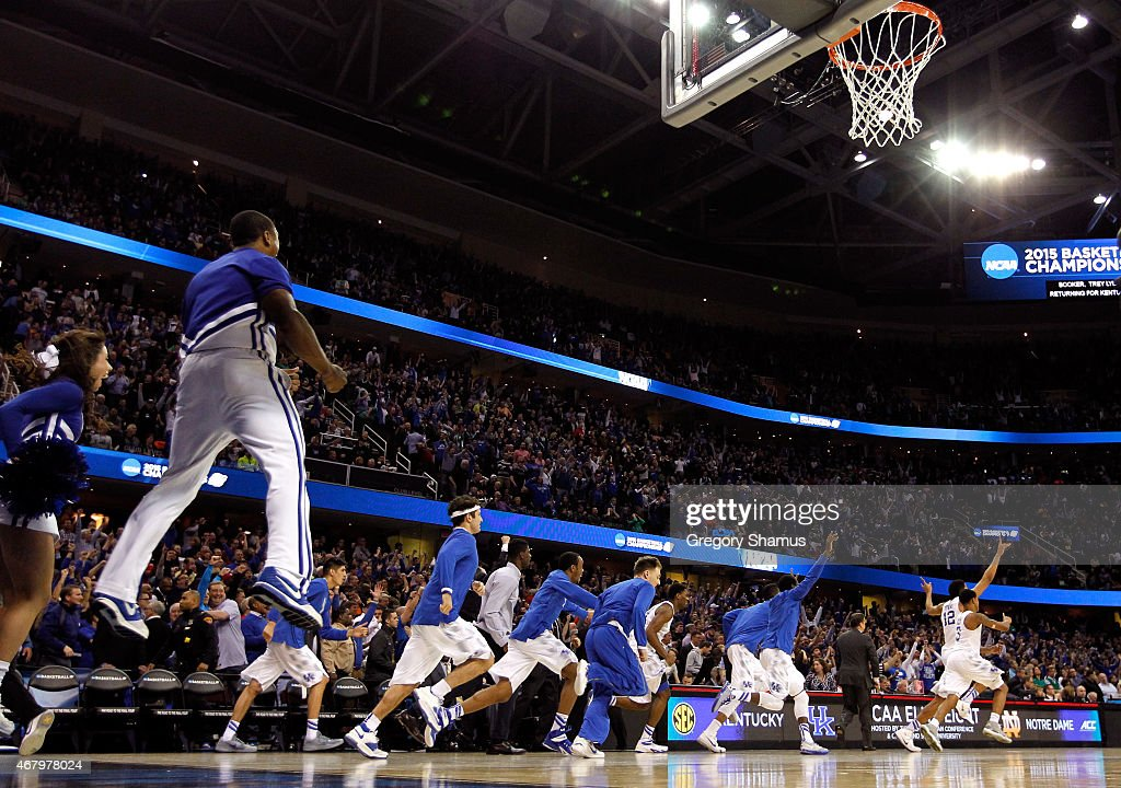 The Kentucky Wildcats bench and cheerleaders celebrate after defeating the Notre Dame Fighting Irish during the Midwest Regional Final of the 2015...