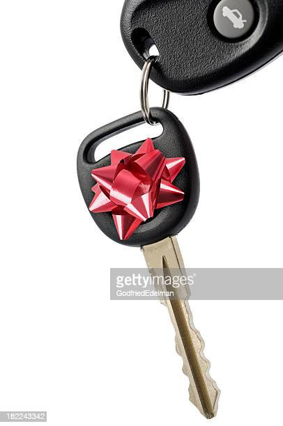 The key of a new car with a gift ribbon isolated on white