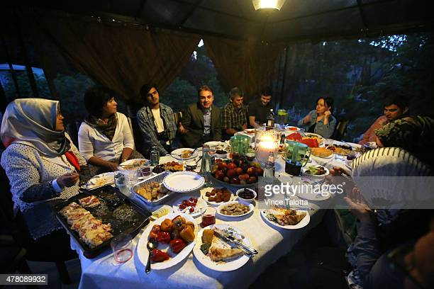 The Khalilov family eating Ramadan dinner with friends and family in their backyard on the second day of Ramadan