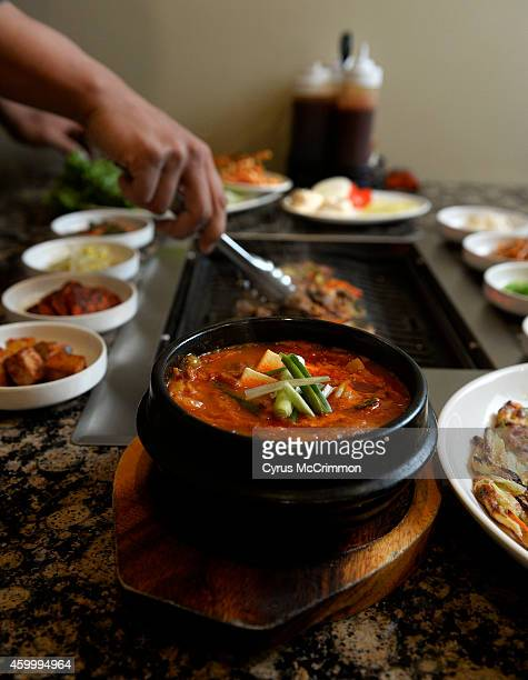 The kimchee cheegae is a hot and spicy soup with beef broth with shredded beef and vegetables with the beef bulgogi on the tabletop grill in the...