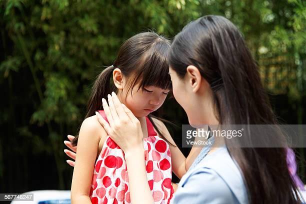 The kindergarten teachers in comfort the sad girl