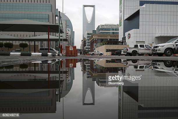 The Kingdom Tower operated by Kingdom Holding Co is reflected in a puddle in Riyadh Saudi Arabia on Saturday Nov 26 2016 Saudi Arabia and the emirate...