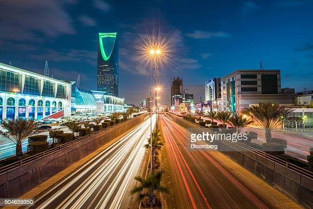 The Kingdom Tower operated by Kingdom Holding Co left stands alongside the King Fahd highway illuminated by the light trails of passing traffic in...